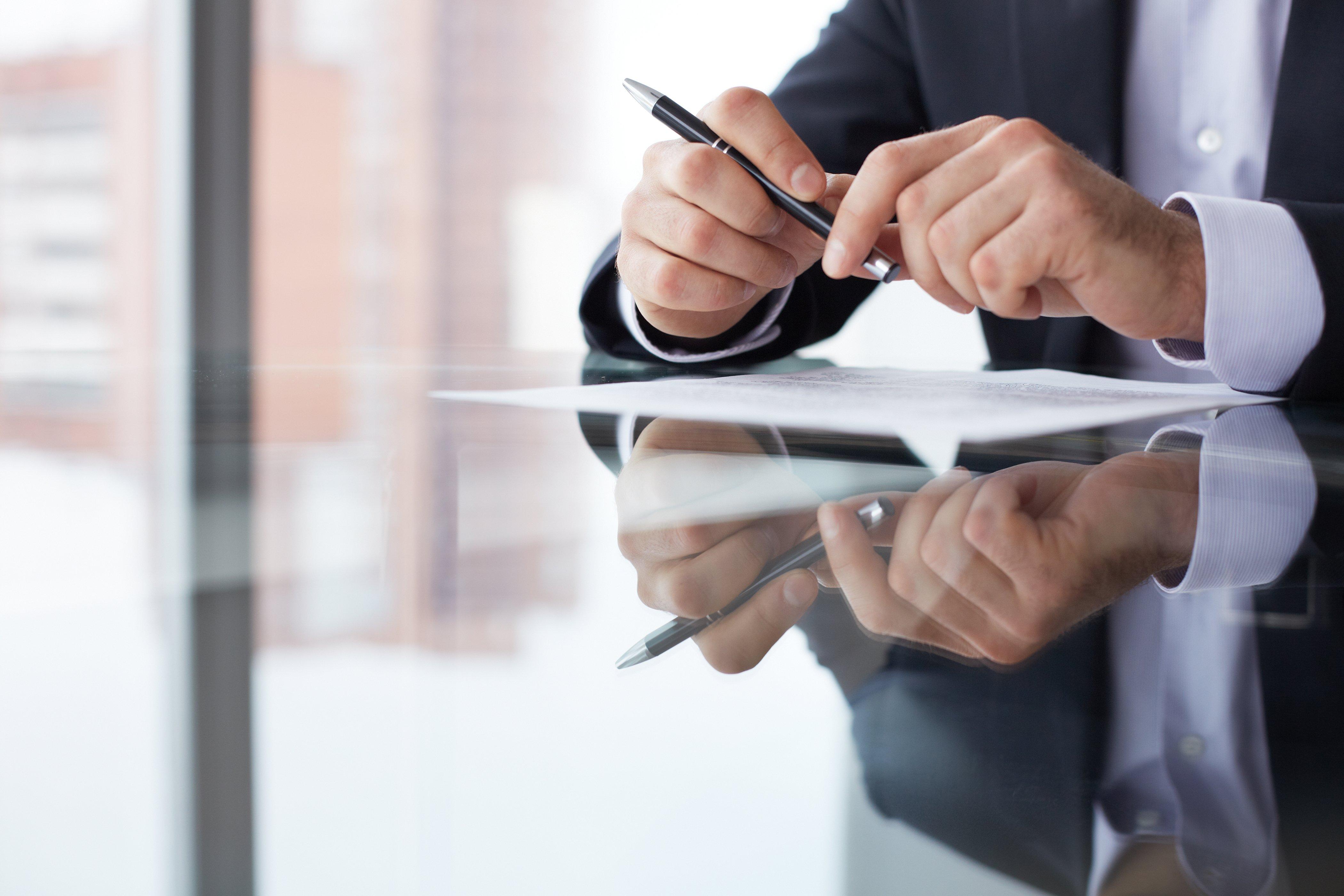 hands-pen-paper-table